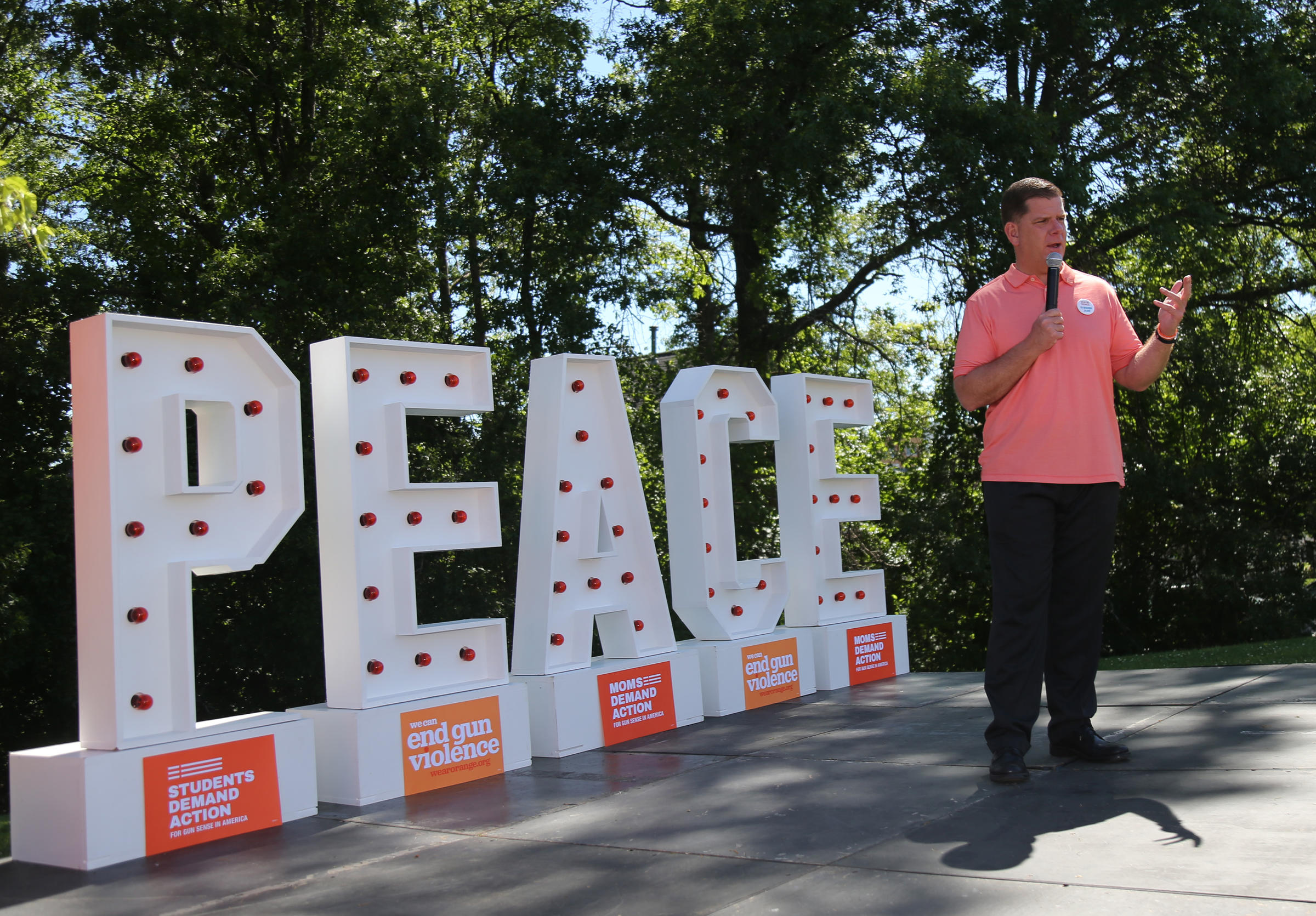 Mayor Walsh speaking at even in front of Peace sign