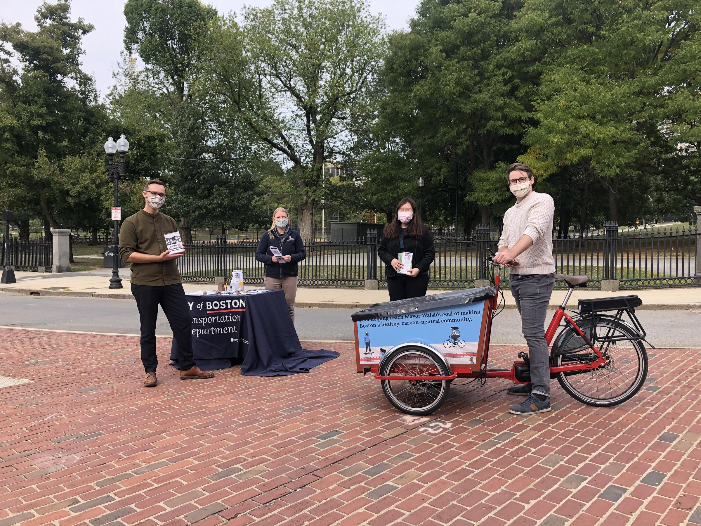 Four people wearing face coverings stand outside on a traffic island. Three people are holding brochures. A table has more materials and is covered with a blue tablecloth that says City of Boston Transportation department. One person stands near a cargo bike.