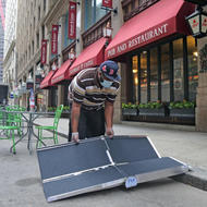Irwin Edwards sets up their new accessibility ramp at Elephant & Castle in downtown Boston. (Mayor's Office Photo by John Wilcox)