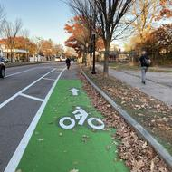 A green bike lane extends forward from view, with a car traveling to the left in a travel lane. Trees line the street to the right, and a person is walking on the sidewalk.